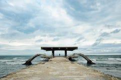 Siluetta della donna su un vecchio ponte abbandonato del mare Immagine Stock