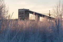 Siluetta della fabbrica che costruisce i conglomerati per la produzione di cemento nell'inverno fotografie stock