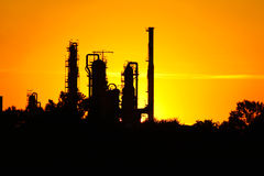 Siluetta della fabbrica della raffineria di petrolio contro il tramonto Fotografie Stock