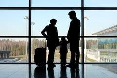 Siluetta della famiglia con bagagli vicino alla finestra Fotografie Stock