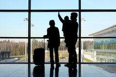 Siluetta della famiglia con bagagli vicino alla finestra Fotografia Stock