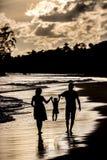 Siluetta della famiglia sulla spiaggia al tramonto Immagine Stock