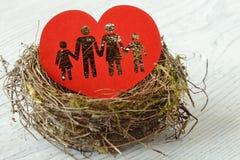 Siluetta della famiglia tagliata nel cuore di carta in un nido - concetto di amore e della famiglia fotografie stock libere da diritti