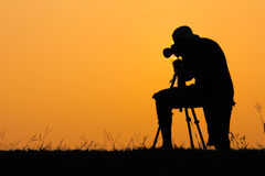 Siluetta della foto della fucilazione del fotografo per un'alba Immagine Stock Libera da Diritti