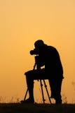 Siluetta della foto della fucilazione del fotografo per un'alba Fotografia Stock Libera da Diritti