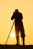 Siluetta della foto della fucilazione del fotografo per un'alba Fotografia Stock