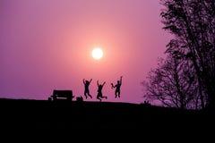 Siluetta della gente che salta contro nell'ambito di un tramonto fotografia stock