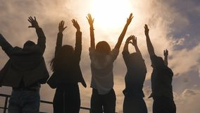 Siluetta della gente che si rallegra e che alza le sue mani un gruppo di riusciti uomini d'affari felici e celebra archivi video