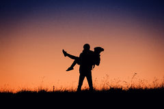 Siluetta della gente divertendosi al tramonto Immagini Stock