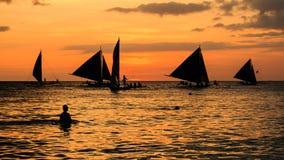 Siluetta della gente e delle barche al tramonto Fotografia Stock