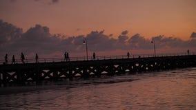 Siluetta della gente irriconoscibile che cammina sul pilastro lungo sopra il fondo del litorale stock footage