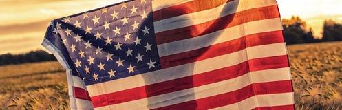 Siluetta della giovane donna che tiene la bandiera di U.S.A. nel campo al tramonto immagine stock libera da diritti
