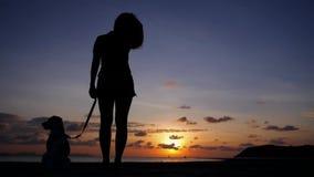 Siluetta della giovane donna con il cane al tramonto a stock footage