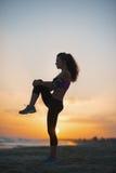 Siluetta della giovane donna di forma fisica che allunga sulla spiaggia al crepuscolo Immagini Stock Libere da Diritti