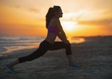 Siluetta della giovane donna di forma fisica che allunga sulla spiaggia al crepuscolo Fotografia Stock Libera da Diritti