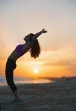 Siluetta della giovane donna di forma fisica che allunga sulla spiaggia al crepuscolo Immagine Stock Libera da Diritti