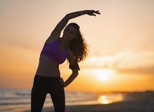 Siluetta della giovane donna di forma fisica che allunga sulla spiaggia al crepuscolo Immagine Stock