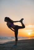 Siluetta della giovane donna di forma fisica che allunga sulla spiaggia al crepuscolo Fotografia Stock