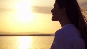 Siluetta della giovane donna sorridente al tramonto sul lago Figura femminile all'ora dorata al rallentatore video d archivio