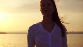 Siluetta della giovane donna sorridente al tramonto sul lago Figura femminile all'ora dorata al rallentatore archivi video
