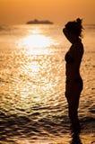 Siluetta della giovane donna sulla spiaggia con la nave nel fondo Fotografia Stock Libera da Diritti