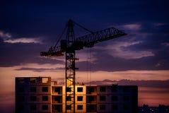 Siluetta della gru e della costruzione al tramonto Fotografia Stock