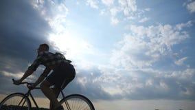 Siluetta della guida del giovane alla bicicletta d'annata con il bello cielo di tramonto a fondo Tipo sportivo che cicla nel Fotografie Stock