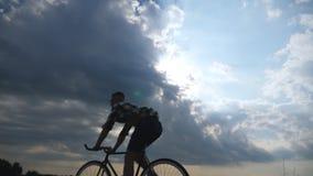 Siluetta della guida del giovane alla bicicletta d'annata con il bello cielo di tramonto a fondo Tipo sportivo che cicla nel Fotografia Stock