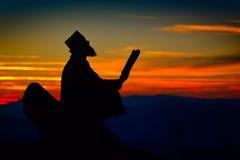 Siluetta della lettura del sacerdote alla luce di tramonto Immagini Stock Libere da Diritti