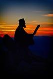 Siluetta della lettura del sacerdote alla luce di tramonto Fotografie Stock Libere da Diritti