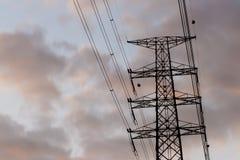 Siluetta della linea ad alta tensione sulla penombra del cielo Fotografia Stock
