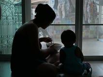 Siluetta della madre asiatica che tiene una ciotola di alimento e che alimenta il suo bambino a casa fotografia stock