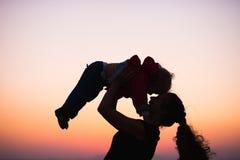 Siluetta della madre che gioca con il bambino nel crepuscolo Fotografia Stock