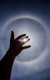Siluetta della mano con l'alone circolare di Sun immagini stock libere da diritti