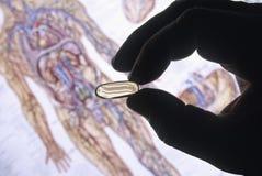 Siluetta della mano con la pillola Immagini Stock