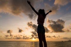 Siluetta della mano della donna su nell'ambito del tramonto Immagini Stock