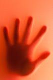 Siluetta della mano su fondo rosso. Fotografia Stock Libera da Diritti
