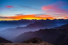 Siluetta della montagna e cielo sbalorditivo al tramonto Immagini Stock