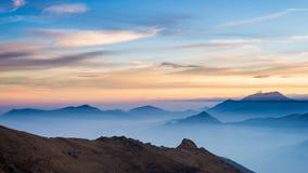 Siluetta della montagna e cielo sbalorditivo al tramonto Fotografie Stock