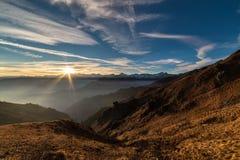 Siluetta della montagna e cielo sbalorditivo al tramonto Fotografia Stock