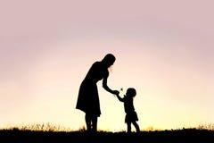 Siluetta della neonata che dà il fiore della mamma al tramonto Fotografia Stock