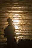 Siluetta della persona che prende il sole in suo Fotografie Stock
