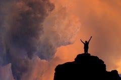 Siluetta della persona sulla roccia al tramonto Fotografia Stock Libera da Diritti
