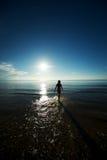 Siluetta della ragazza che cammina nel mare Immagini Stock Libere da Diritti