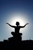 Siluetta della ragazza che fa le pose di yoga Fotografia Stock