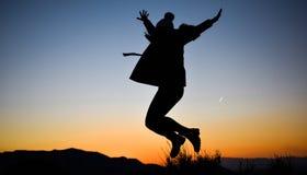 Siluetta della ragazza che salta in mezzo alla natura sull'inverno contro il tramonto fotografia stock