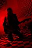 Siluetta della ragazza che si inginocchia e che gioca chitarra elettrica Fotografie Stock Libere da Diritti