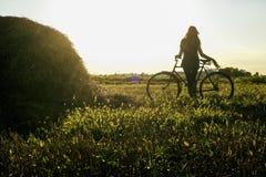 Siluetta della ragazza che si siede sulla bicicletta in un campo soleggiato di estate all'Unione Sovietica immagini stock libere da diritti