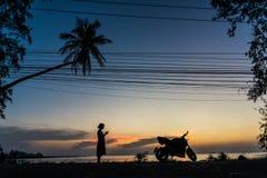 Siluetta della ragazza con il telefono ed il motociclo sul fondo di tramonto sull'isola tropicale fra le palme fotografia stock libera da diritti