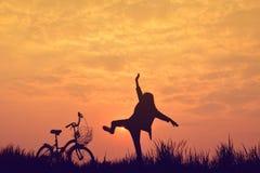 Siluetta della ragazza con la bicicletta sul campo di erba Fotografia Stock Libera da Diritti